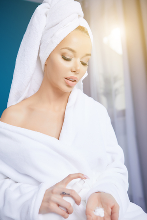 beautiful young woman wearing a towel and a white bathrobe and applying body lotion, in bed at home Stock Photo