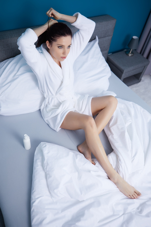 young woman in bathrobe sitting on bed at home