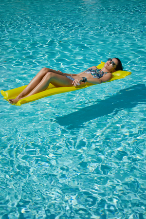 suncare: A woman in the pool floats on a blown mattress Stock Photo