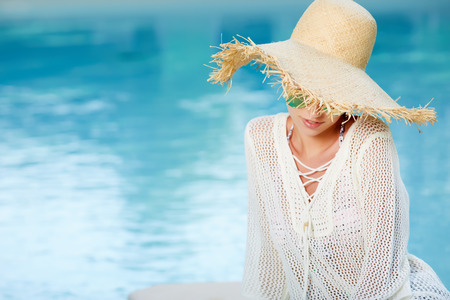 sun energy: Beautiful girl in a  dress and sunhat sits next a resort pool Stock Photo