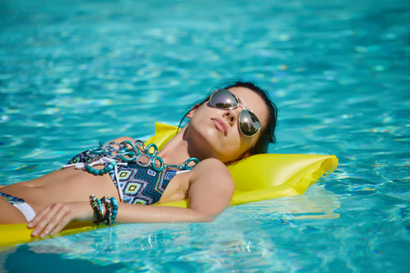 woman bath: A woman in the pool floats on a blown mattress Stock Photo