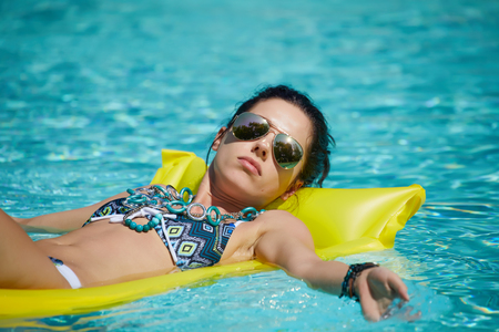 A woman in the pool floats on a blown mattress Stock Photo