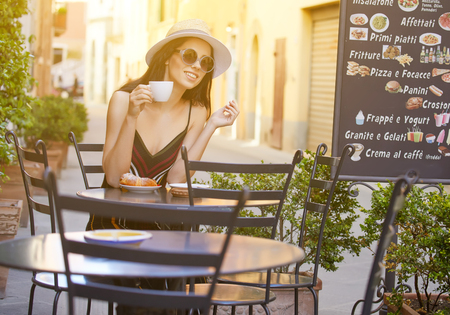 Young woman having italian breakfast with croissant and coffee at the cafe on the street Archivio Fotografico