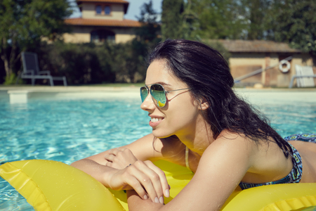 Colorful portrait of pretty young woman in red swimsuit lying on yellow inflatable mattress at swimming pool.