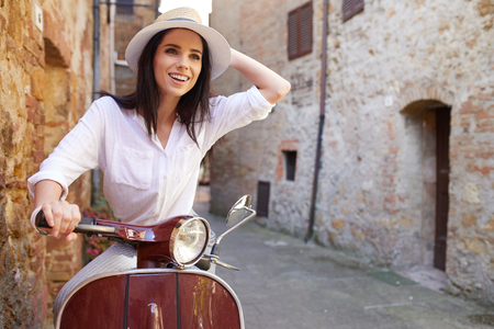 beautiful girl in a hat in a white t-shirt and hat posing on a vintage scooter in Italy fashion clothing and accessories bracelet on her arm