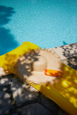 sunhat: Hat and bottle of sun cream by the pool