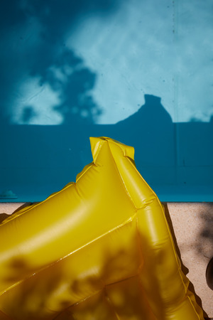 yellow inflatable raft on pool, vacation background