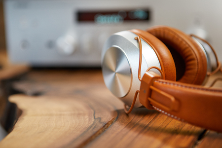 Vintage Headphones lie on a wooden table. Background amplifier hifi Stock Photo