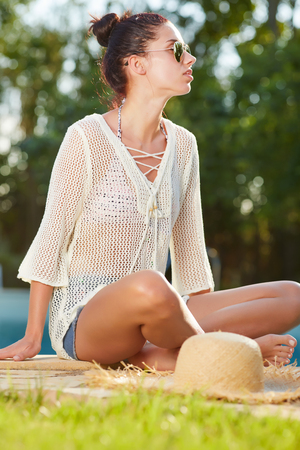 sunburnt: Young woman sun bathing in spa resort swiming pool