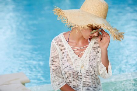 woman bath: Image of a woman sitting by the pool side and smiling over her shoulder