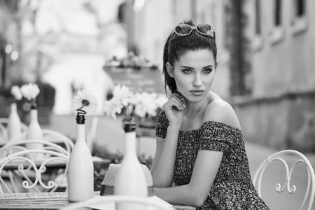 woman sitting at the cafer on the famous street with local food markets in Italy city. BW concept Zdjęcie Seryjne