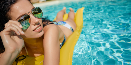 Beautiful young smiling woman in the pool  Stock Photo