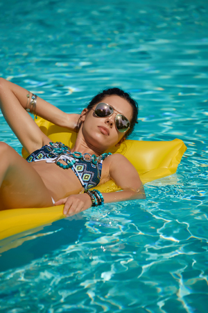 colorfully: Beautiful young smiling woman in the pool