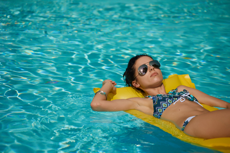 colorfully: Beautiful young smiling woman in the pool  Stock Photo