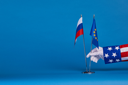 sabotage: Two flags and hand on a blue background, the political concept