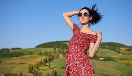 toskana: View of a girl in red dress in Tuscany hills, Italy