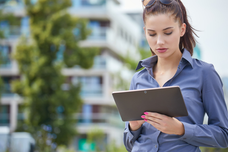Smiling businesswoman using electronic tablet outside Stock Photo
