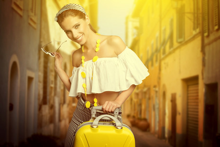 Elegant woman with a suitcase travel and umbrella on street of italian city