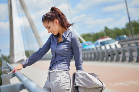 Portrait of a young businesswoman standing with coffee cup and tablet on the modern bridge