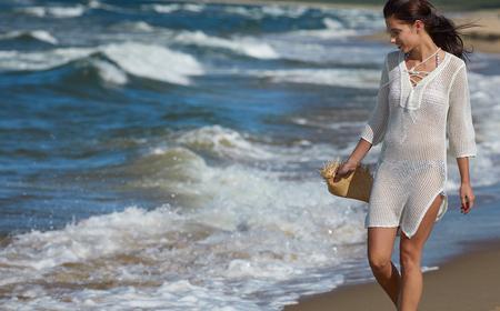 Mujer joven que recorre en el agua que desgasta el vestido blanco de la playa Foto de archivo - 82268374