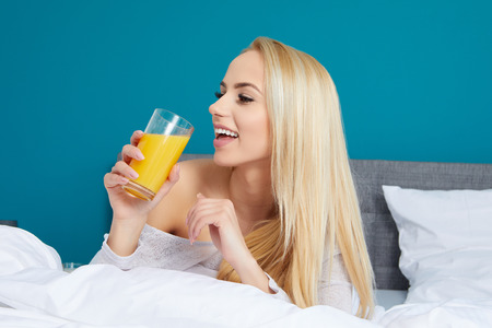 Attractive woman drinking orange juice sitting on her bed photo