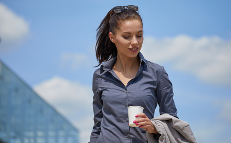 Beautiful young businesswoman with a disposable coffee cup, drinking coffee, against urban city background.