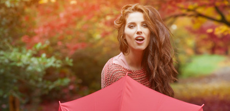 Portret van een herfst vrouw over rode en gouden bladeren