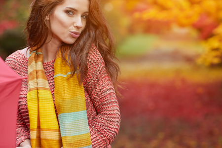 Portrait of an autumn woman over red and golden leaves Stock Photo