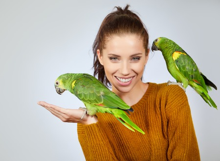 Two bird, cute parrots, sit on woman. Studio shoot