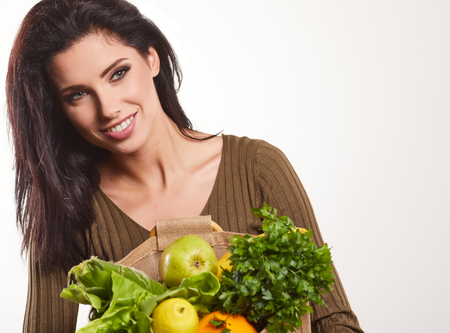 Happy young woman holding a paper shopping bag full of vegetable food