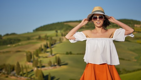 Tuscany tourism - woman in red dress visits Tuscan countryside in Siena province, Italy. photo