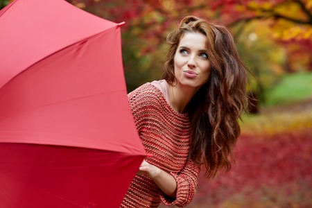 Autumn woman in autumn park with red umbrella, scarf and leather gloves photo