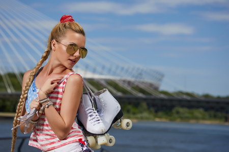 hair roller: Portrait of a beautiful young blonde girl in a vintage roller skates, wearing shorts, golfs and a T-shirt. Hot summer day. Outdoor. Stock Photo