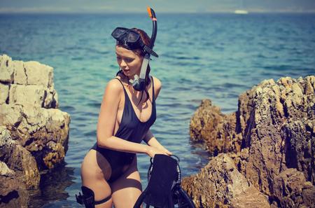 Sexy beach bikini girl wearing scuba gear and crossbow