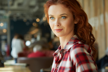 marketing online: Beautiful red-haired woman in cafe. Blogger work concept