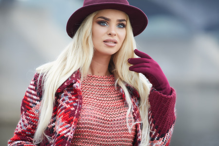 Close up portrait of elegant pretty blonde woman posing at autumn cold day