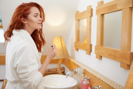 Body care series - Beautiful young woman applying cream in the bathroom