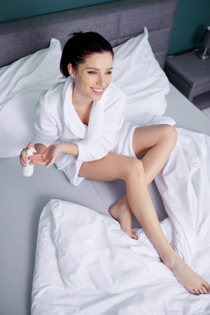 beautiful woman putting creme on her legs while sitting in bedroom