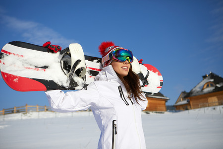 Sporty female holds snowboard in mountains Stock Photo