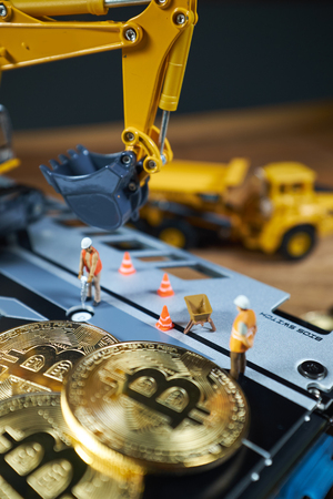 A little miner is digging on graphic card with golden coin. bitcoin mining and crypto currency concept. Stock Photo