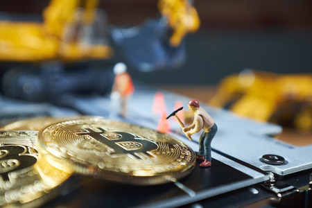 A little miner is digging on graphic card with golden coin. bitcoin mining and crypto currency concept. Banque d'images