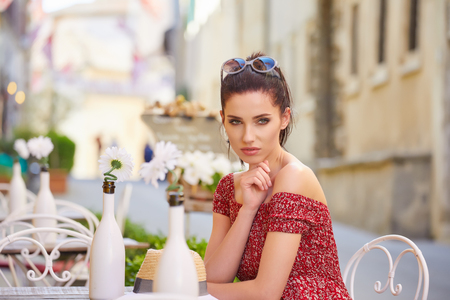 Portrait of beautiful woman sitting in outdoors cafe in Italy, drinking coffee