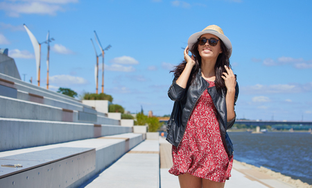 Portrait of happy smiling woman standing on the square on sunny summer or spring day outside, cute smiling woman looking at you, attractive young girl enjoying summer Stock Photo
