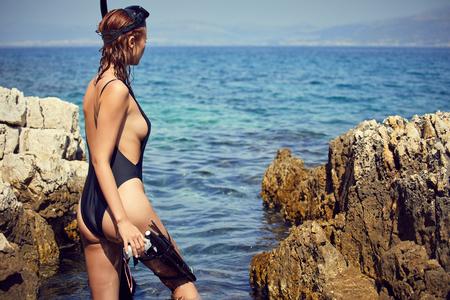 woman holding pink snorkel fins in black bikini on vacation Foto de archivo