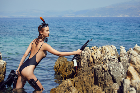 woman holding pink snorkel fins in black bikini on vacation Standard-Bild