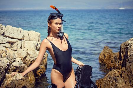 woman holding pink snorkel fins in black bikini on vacation Standard-Bild