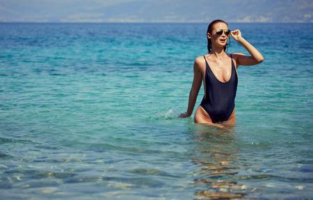 beautiful young woman in bikini bathing and splashing happily in the sea at the resort