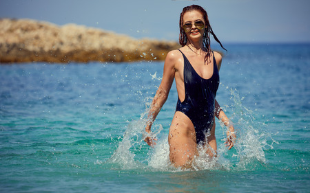beautiful young woman in bikini bathing and splashing happily in the sea at the resort