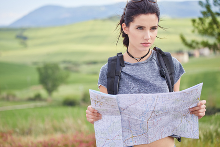 woman holding paper map finding right tourist route