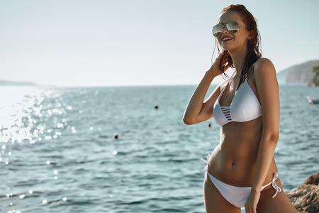 Sexy beautiful woman in white swimwear and creative hat at the sea coast. Sunset soft sun light Stock Photo